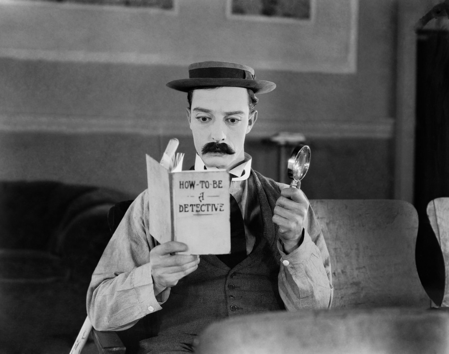 1924: American comedian Buster Keaton (1895-1966) armed with only a magnifying glass and a copy of 'How To Be A Detective' hopes to become a great detective in the film 'Sherlock Junior'.